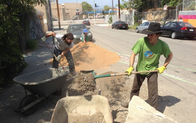 Thiago and Peter shoveling gravel into wheelbarrows to transport it into the LAEV courtyard.