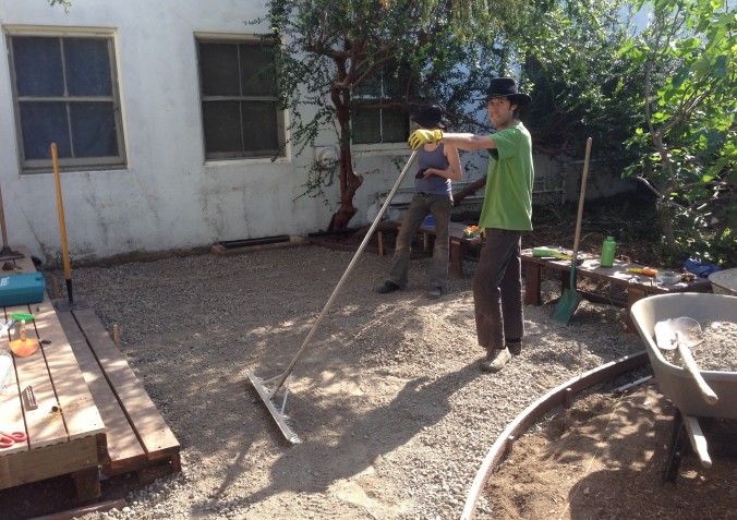 The lower layer of gravel was spread out in the form area. Peter does some raking here.